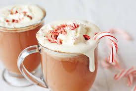mug of hot chocolate with whip cream and candy cane